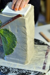 Adding decoration by pressing a leaf into the fine stoneware.